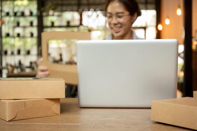 Mujeres jovenes del negocio de lanzamiento que trabajan en el ordenador portátil con el paquete en la tabla. Foto Premium
