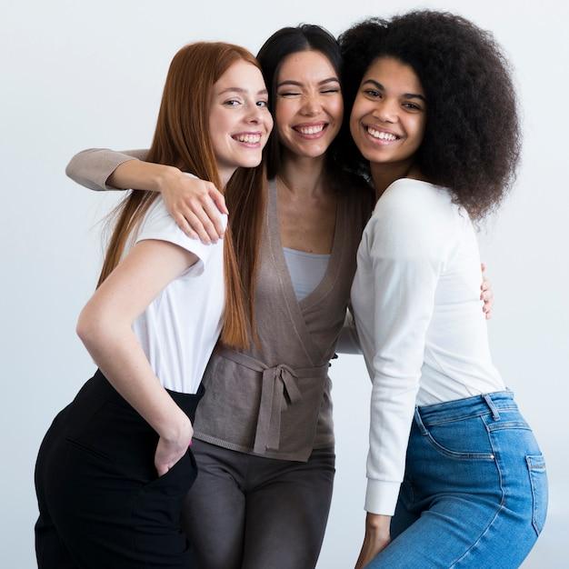 Mujeres jóvenes positivas sonriendo juntos Foto gratis