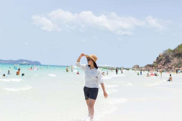Las mujeres jóvenes que viajan se relajan en la playa en verano Foto Premium