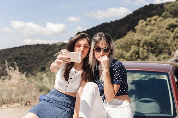 Mujeres jóvenes sentados en coche posando para autorretrato Foto gratis