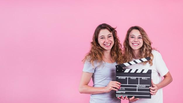 Mujeres jóvenes sonrientes que sostienen el tablero de chapaleta en manos contra el contexto rosado Foto gratis
