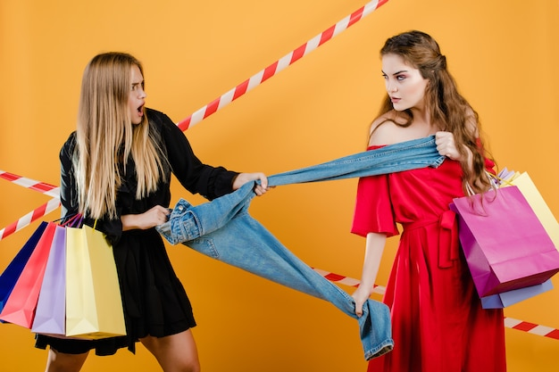 Mujeres jóvenes vistiendo vestidos peleando por un par de jeans con bolsas de compras aisladas sobre amarillo Foto Premium