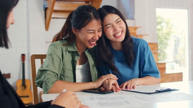 Mujeres lesbianas asiáticas lgbtq pareja firman contrato en casa Foto gratis