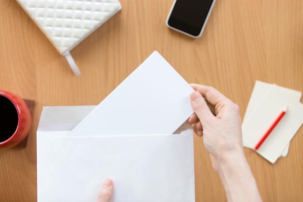Mujeres manos sosteniendo un sobre con una hoja sobre la for Follando en la oficina gratis