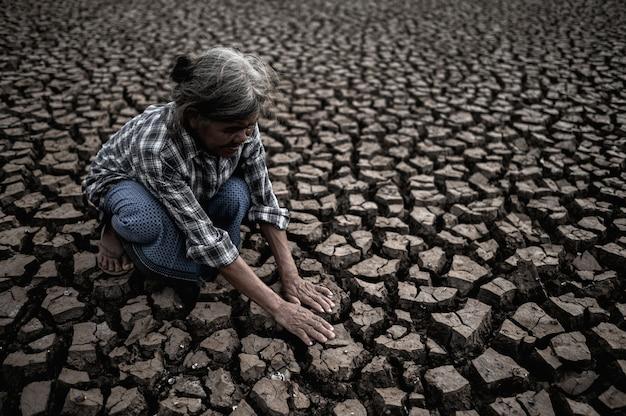 Las mujeres mayores están sentadas mirando sus manos, tocando el suelo en clima seco, el calentamiento global Foto gratis
