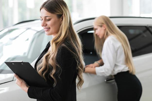 Mujeres mirando a otro lado en el showroom de automóviles Foto gratis