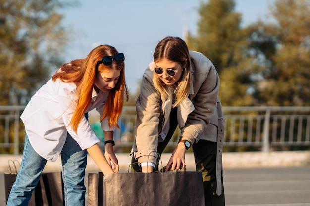 Mujeres de moda joven con bolsas de la compra en el estacionamiento Foto gratis