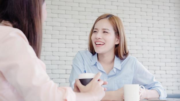 Mujeres de negocios asiáticas que disfrutan de tomar café caliente, discuten sobre el trabajo y chismes de chat Foto gratis