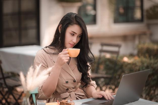 Mujeres de negocios que se sientan bebiendo café y sonriendo feliz relajándose en el parque Foto Premium