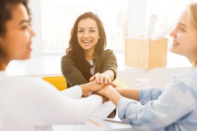 Mujeres de negocios sonrientes estrechándole la mano Foto gratis