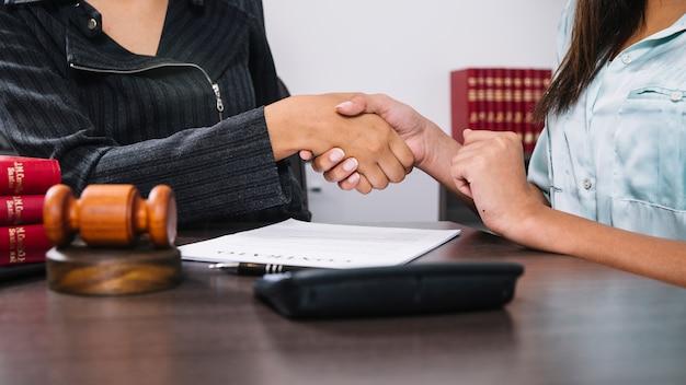 Mujeres negras dándose la mano en la mesa con documento, calculadora y martillo Foto gratis