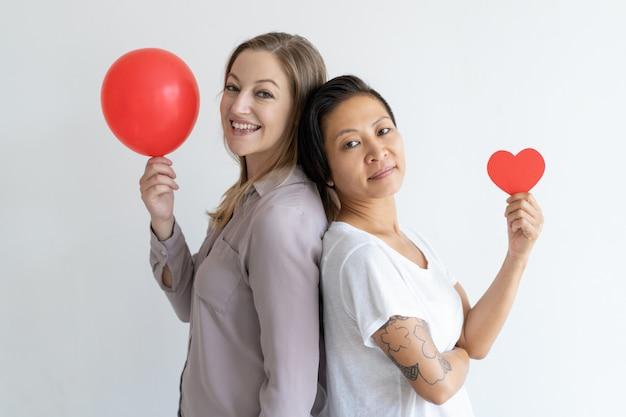 Mujeres de pie espalda con espalda con globo rojo y corazón de papel. Foto gratis