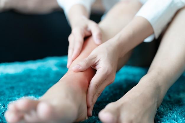 Mujeres en la pierna, lesión en el tobillo / dolor, las mujeres tocan el dolor en la pierna del tobillo Foto Premium