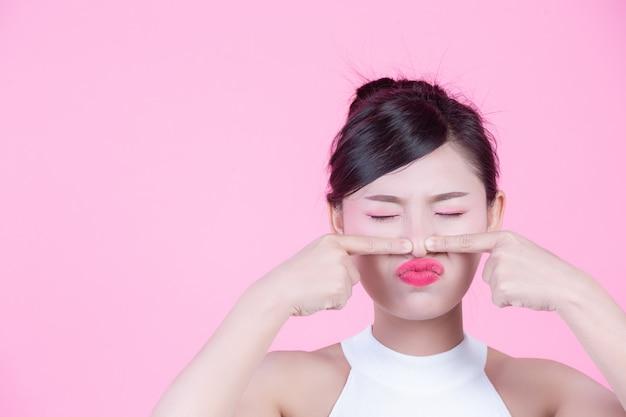 Mujeres con problemas faciales de la piel - mujeres jóvenes infelices que tocan su piel sobre un fondo rosa. Foto gratis