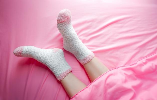 Mujeres que llevan calcetines por la mañana del invierno y el fondo de las mantas. Foto Premium