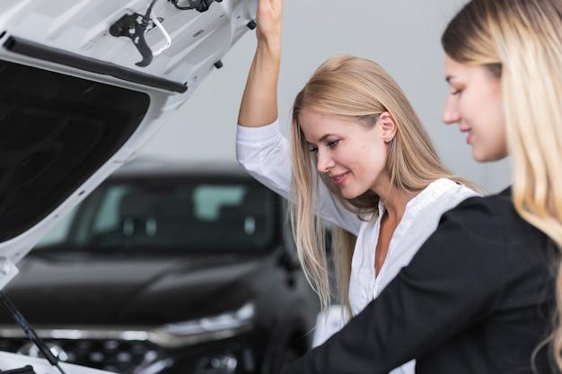 Mujeres revisando el automóvil en el showroom Foto gratis