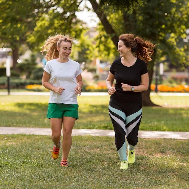 Mujeres en ropa deportiva corriendo juntos afuera Foto gratis