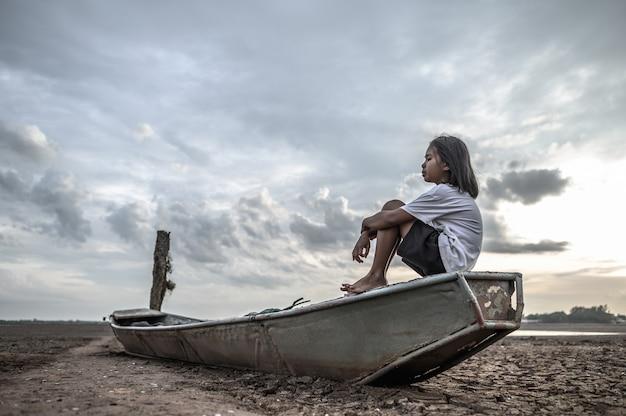 Las mujeres se sientan abrazando sus rodillas en un bote de pesca y miran el cielo en tierra firme y el calentamiento global Foto gratis