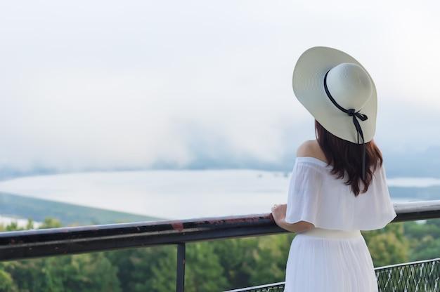 Mujeres con un sombrero de ala blanca retrocediendo para mirar la vista. Foto Premium