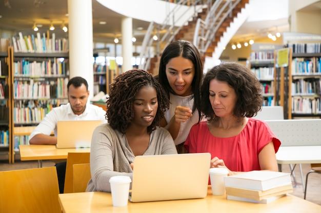 Mujeres sonrientes que trabajan con la computadora portátil en la biblioteca pública Foto gratis