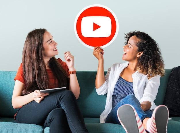 Mujeres sosteniendo un icono de youtube Foto gratis