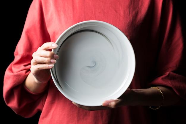 Las mujeres sostienen platos blancos en sus manos. Foto Premium
