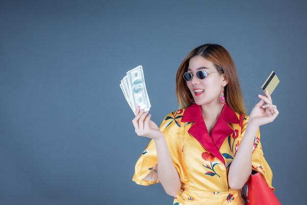 Mujeres con tarjetas inteligentes y dinero. Foto gratis