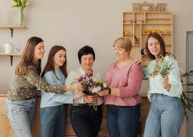 Mujeres de todas las edades con flores en flor Foto gratis
