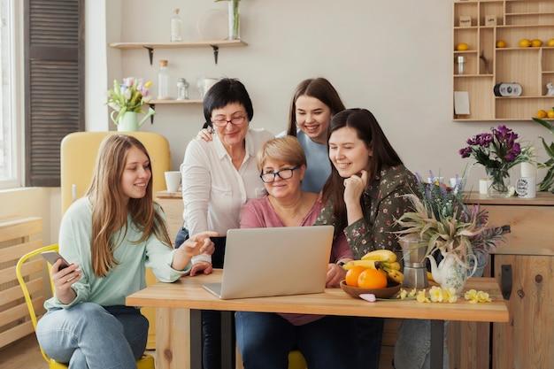 Mujeres de todas las edades sentadas en un escritorio de oficina. Foto gratis