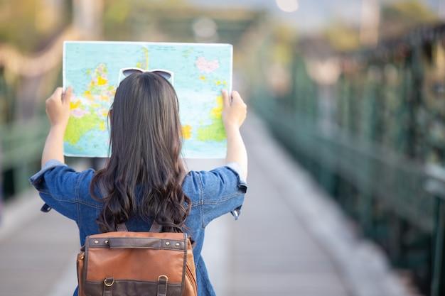 Mujeres turistas en mano tienen un feliz mapa de viaje. Foto gratis