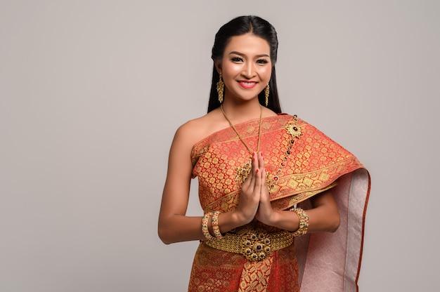 Mujeres vestidas con ropa tailandesa que rinden respeto, símbolo sawasdee Foto gratis