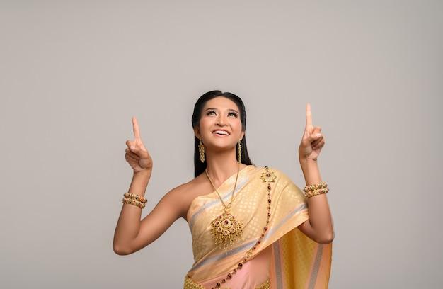 Mujeres vestidas con trajes tailandeses que son simbólicos, señalando con el dedo Foto gratis