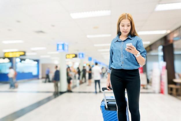 Mujeres viajeras asiáticas que buscan un vuelo en un teléfono inteligente en la terminal del aeropuerto concepto de viaje Foto Premium