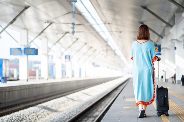 Mujeres viajeras en plataforma con equipaje y pertenencias en la estación de tren. Foto Premium