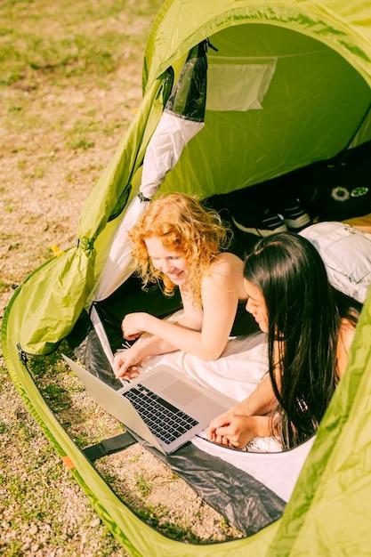 Mujeres viendo la película en la computadora portátil en la tienda Foto gratis