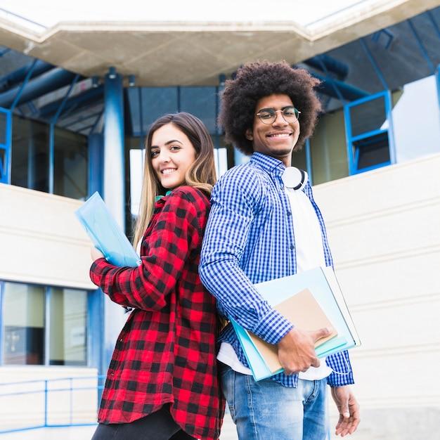 Multi étnica masculina y femenina de pie espalda con espalda frente a campus universitario Foto gratis