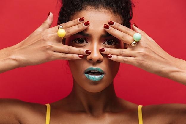 Multicolor joven mulata con maquillaje de moda mirando a la cámara a través de los dedos con anillos, sobre la pared roja Foto gratis