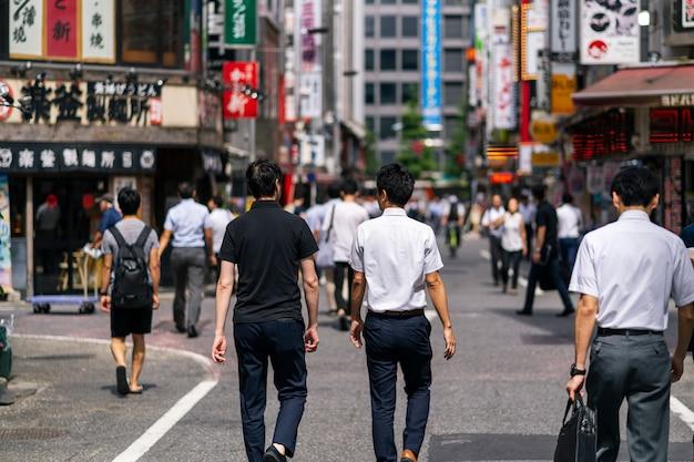 Las multitudes pasan por kabukicho en el distrito de shinjuku, un área de entretenimiento y luz roja. Foto Premium
