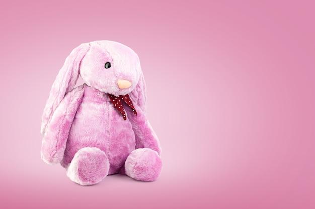 Muñeca de conejo rosa con orejas grandes sobre fondo dulce Foto Premium