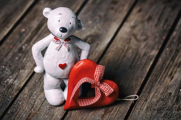 Muñeca de oso blanco con corazón de pie sobre fondo de madera vieja. concepto de san valentín. Foto Premium