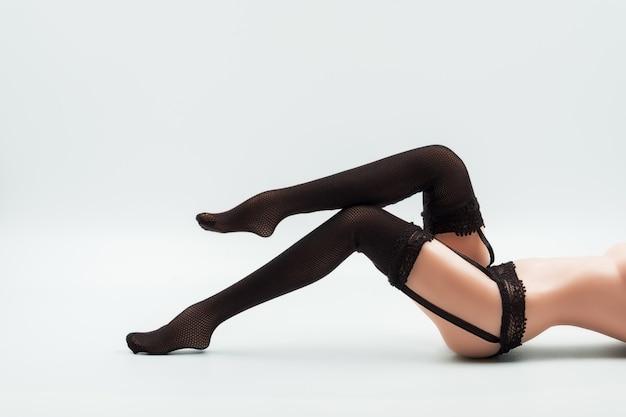 Muñeca sexy de silicona femenina en lencería de encaje negro y medias Foto Premium