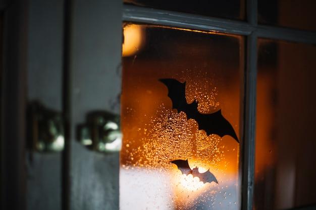 Murciélagos decorativos de halloween en la ventana con gotas de lluvia Foto gratis