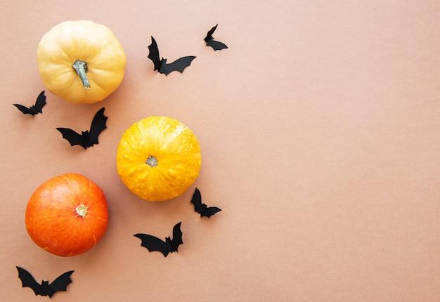 Murciélagos de halloween y calabazas sobre fondo marrón Foto Premium