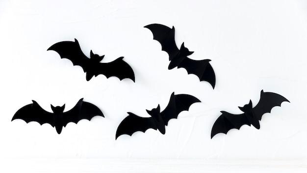 Murciélagos de papel colgando en la pared Foto gratis