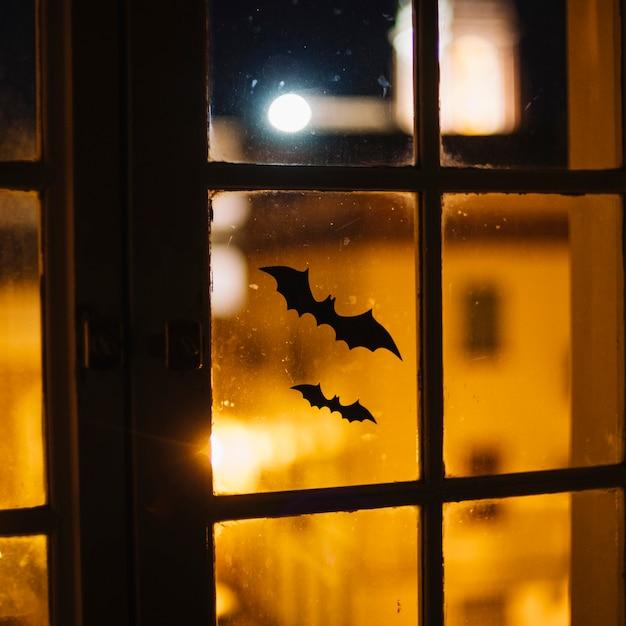 Murciélagos de papel de halloween pegados en la ventana Foto gratis