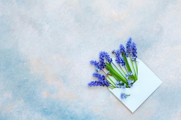 El muscari azul florece en el sobre de papel azul en el fondo del cielo azul Foto Premium
