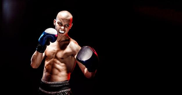 Muscular luchador de muay thai golpeando en la oscuridad Foto Premium