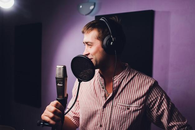 Música, espectáculo, personas y concepto de voz: cantante masculino con auriculares y micrófono cantando una canción en el estudio de grabación de sonido. Foto Premium
