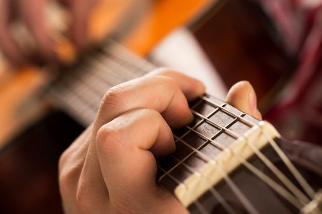 Música, primer plano. músico sosteniendo una guitarra de madera Foto gratis