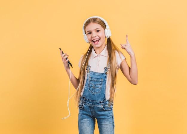 Música que escucha de la muchacha alegre en el auricular que hace la muestra de la roca contra fondo amarillo Foto gratis